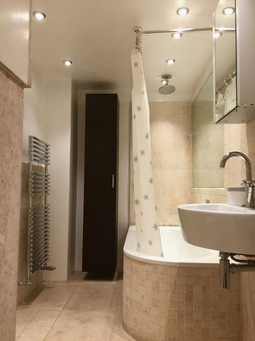 Private bathroom, with bath tube, shower and heated towel rail.