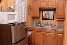 The kitchenette offers a mini fridge, dishes, silverware, cups, electric skillet, toaster,  Keurig, cooking utensils. There is a fire extinguisher under the sink & a First aid kit above the sink
