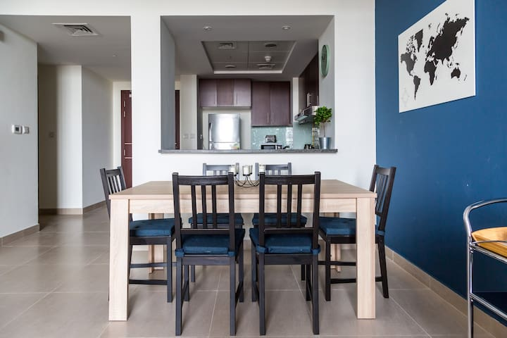 The living room and the kitchen are separated by the dining area that includes a wooden table with sitting spaces for 6 people