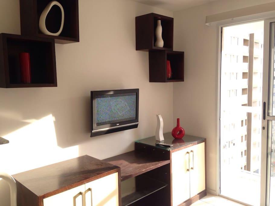 Sala de estar, com móveis, decoração e televisão.