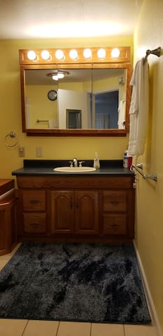 Bathroom with plenty of light, hairdryer, towels, body wash, shampoo, and conditioner.