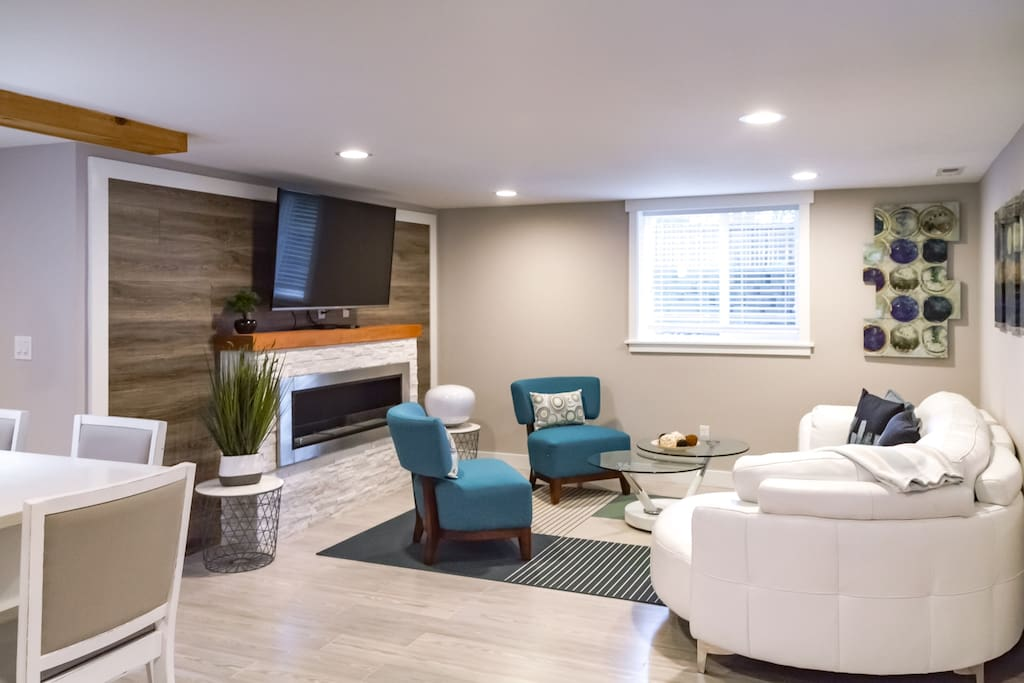"The contemporary living space includes accent wall, fireplace, 48"" smart TV and ample comfortable seating"