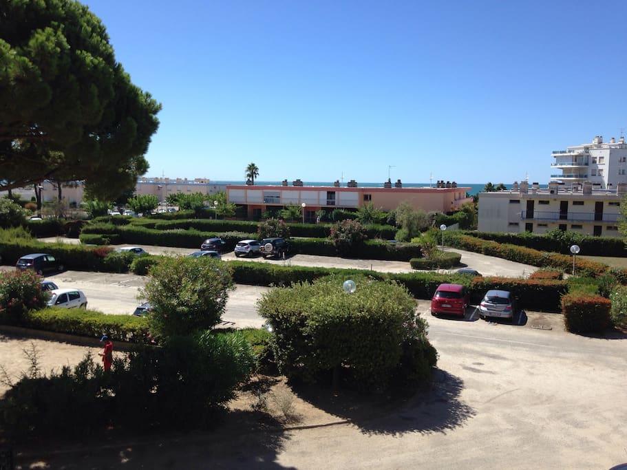 Vu de la loggia sur le parking sécurisé et la mer