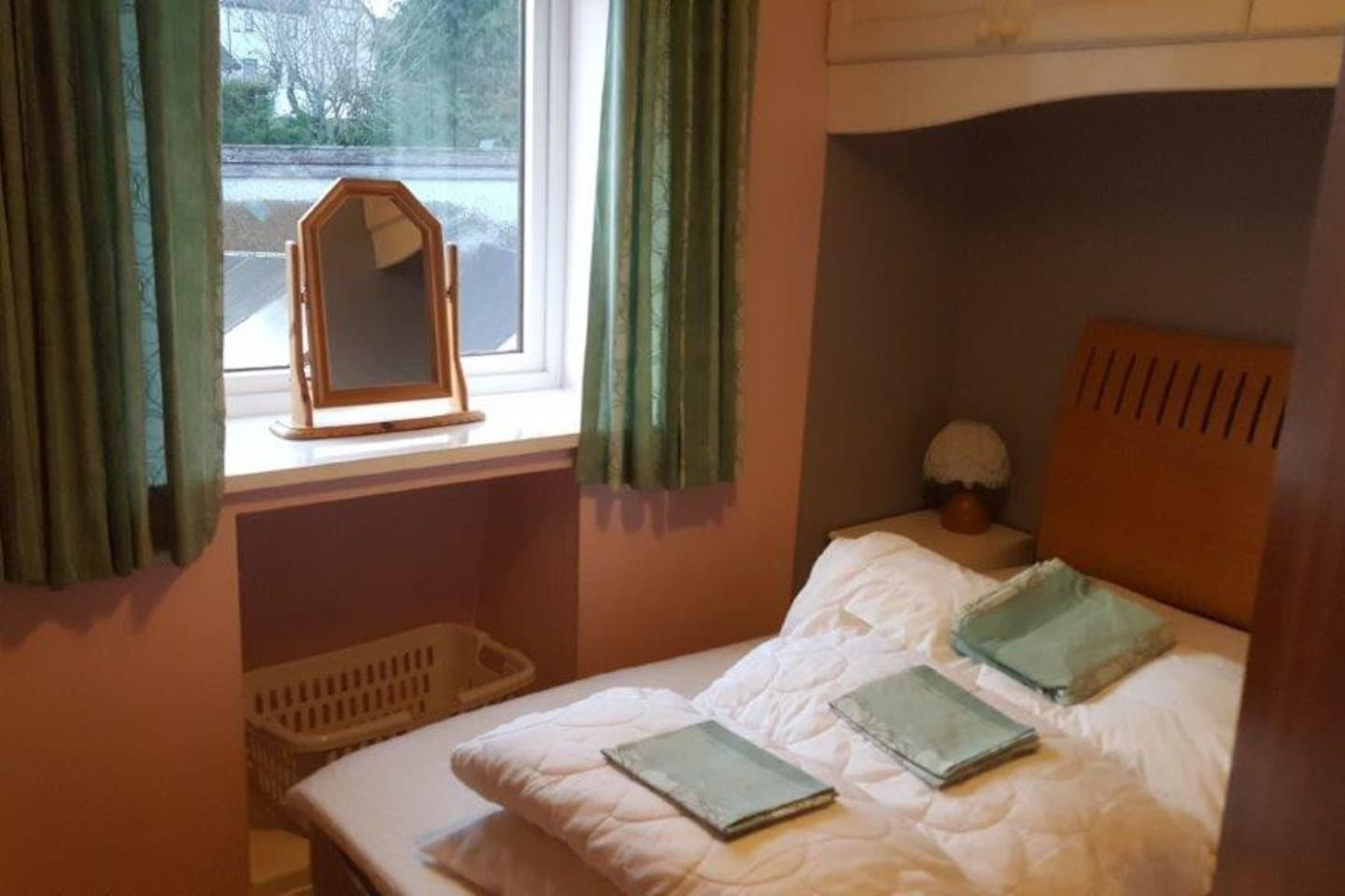 Double bed in bedroom with cupboards over bed