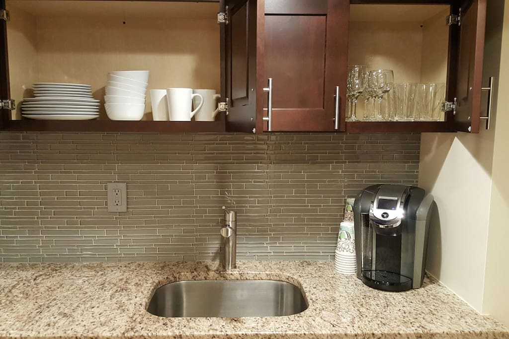 Fully stocked kitchen with flatware, pots, cooking utensils and Keurig coffee maker.