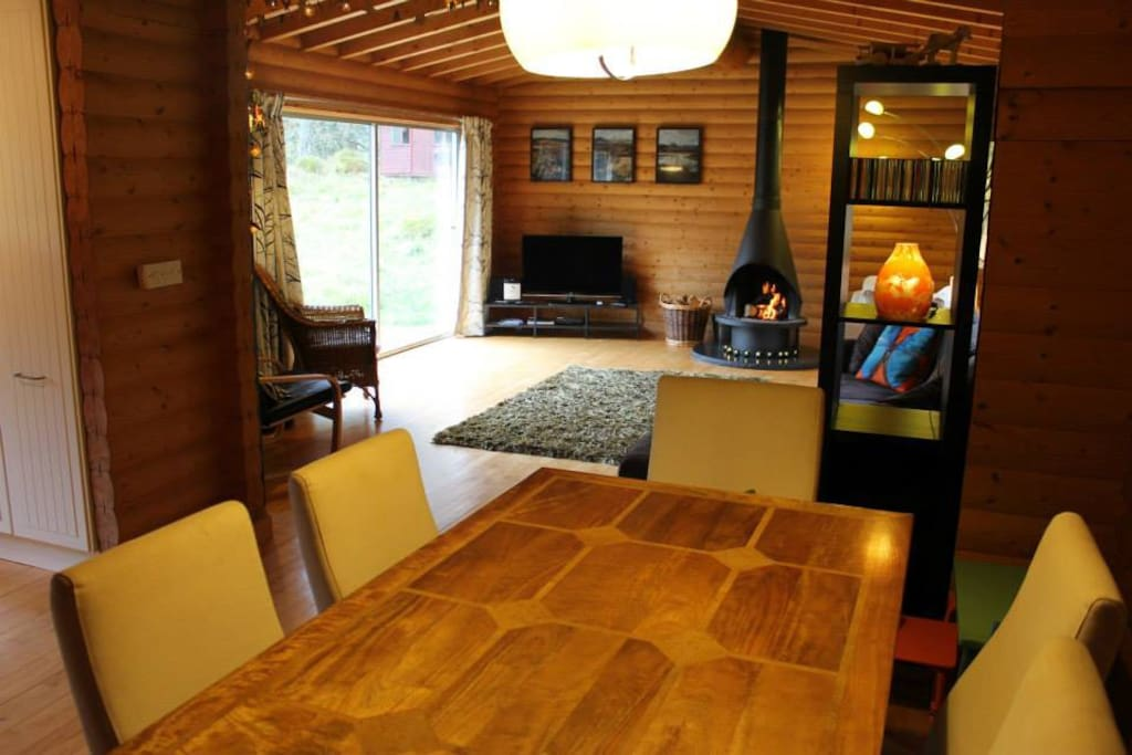 Spacious kitchen-dining-living area with log fire, and views over the patio to the garden and woods