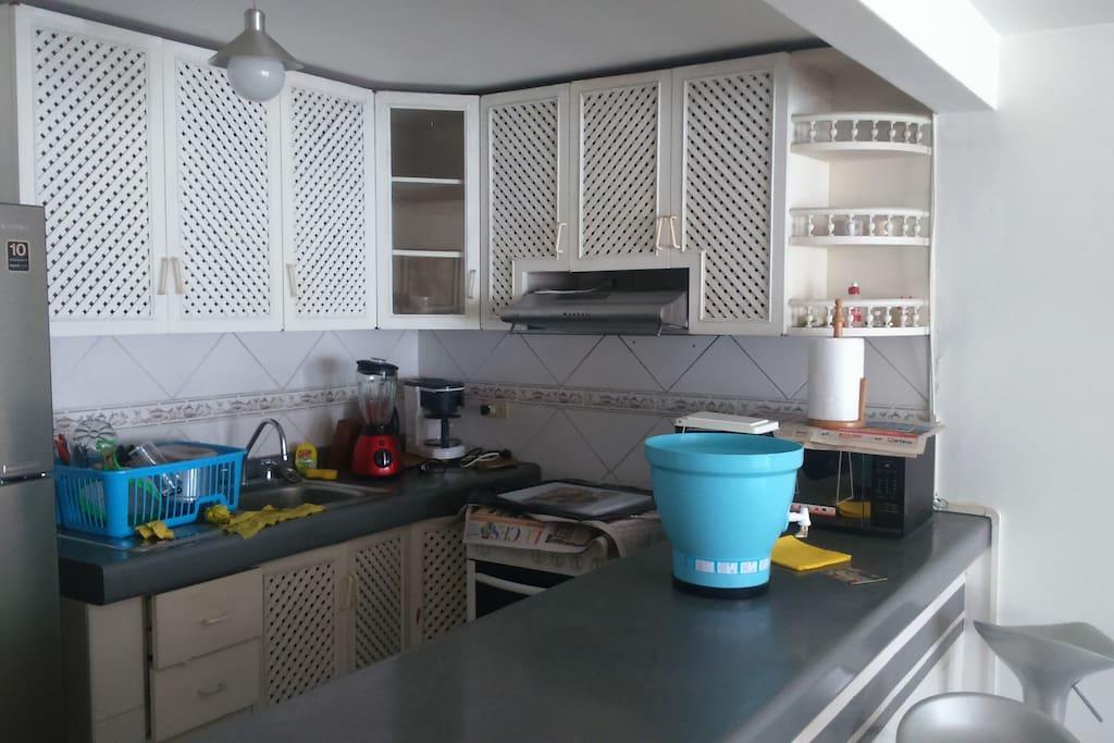 Cocina completa con extractor de grasa con repostero en 2 filas, bar con 3 sillas giratorias, y al lado su lavandería.
