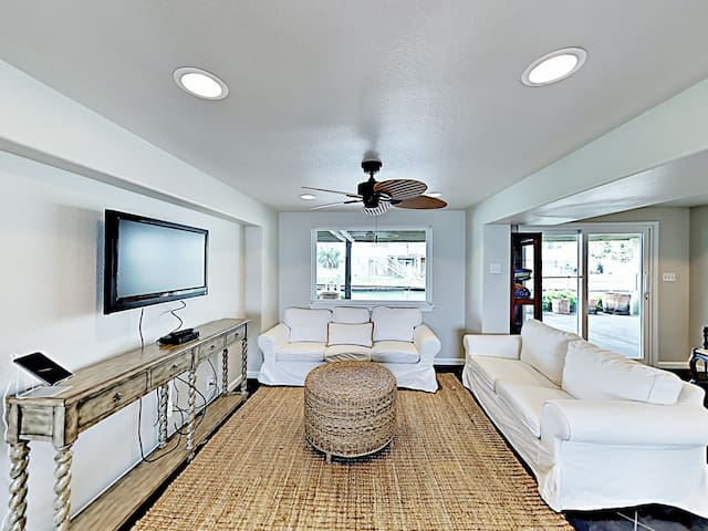 """Unwind in a main living area with seating for 9 and a 50"""" wall-mounted TV."""