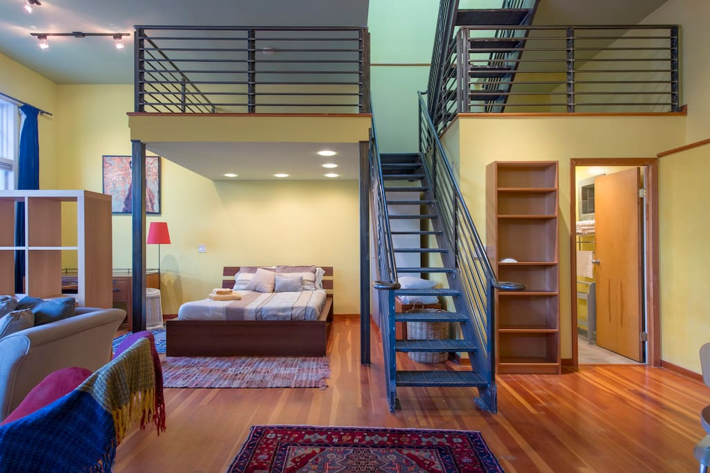 A metal staircase leads to two nooks overlooking the loft.