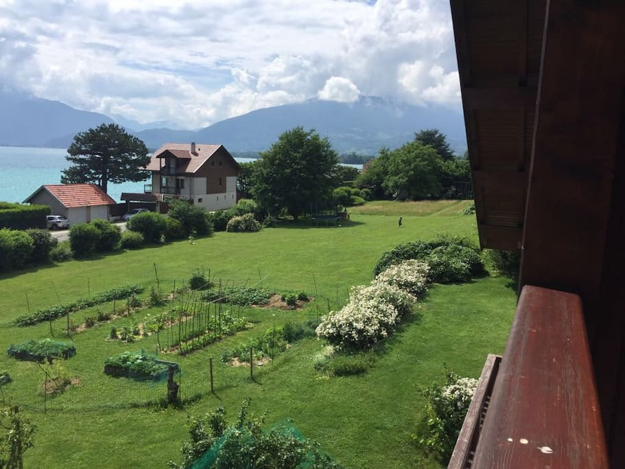 Vue du balcon sur le lac, les montagnes et le potager.