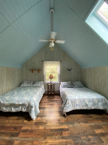 Upstairs bedroom with 2 double beds, skylight and new flooring.