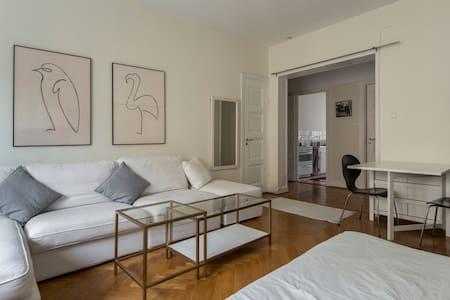 Stort, ljust rum med soffa, matbord och två sängar - Stockholm