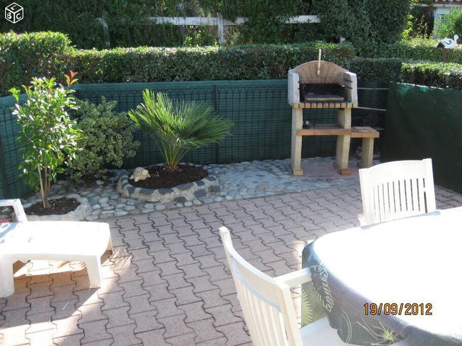 La terrasse avec salon de jardin et barbecue