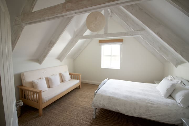 Upstairs bedroom with double bed and sleeper couch.