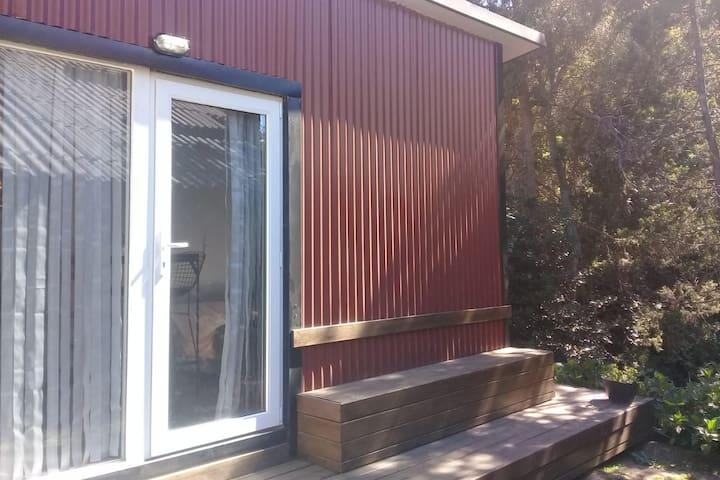 Mini casa con un deck para disfrutar tu estadía.