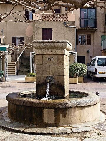 La fontaine trône sur la place centrale du village
