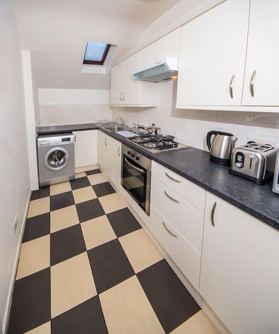 Kitchen with washing machine, oven, kitchen ware, cutlery and glassware.