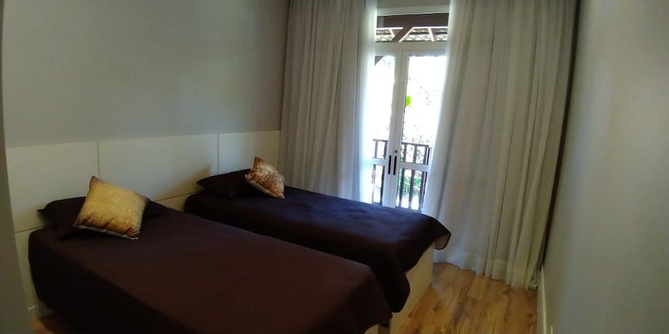 Vista do quarto existente no andar superior com armário embutido instalado, além de uma cama de solteiro e uma bicama.