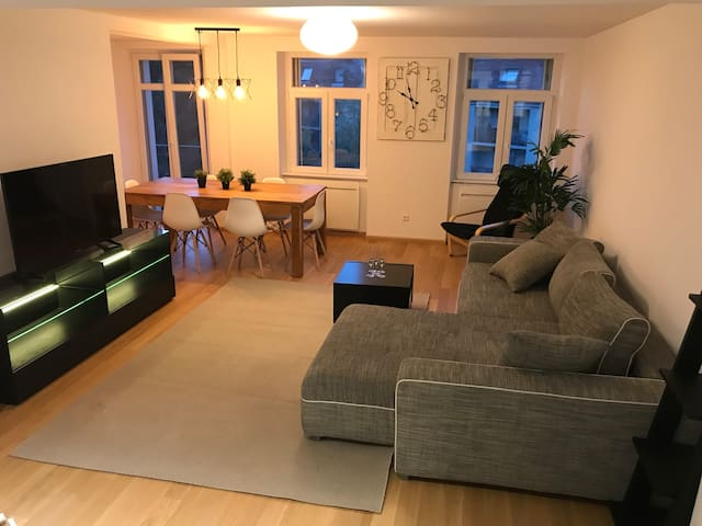 Living with big oak table convertible sofa and 4k big TV. This is open with the kitchen.