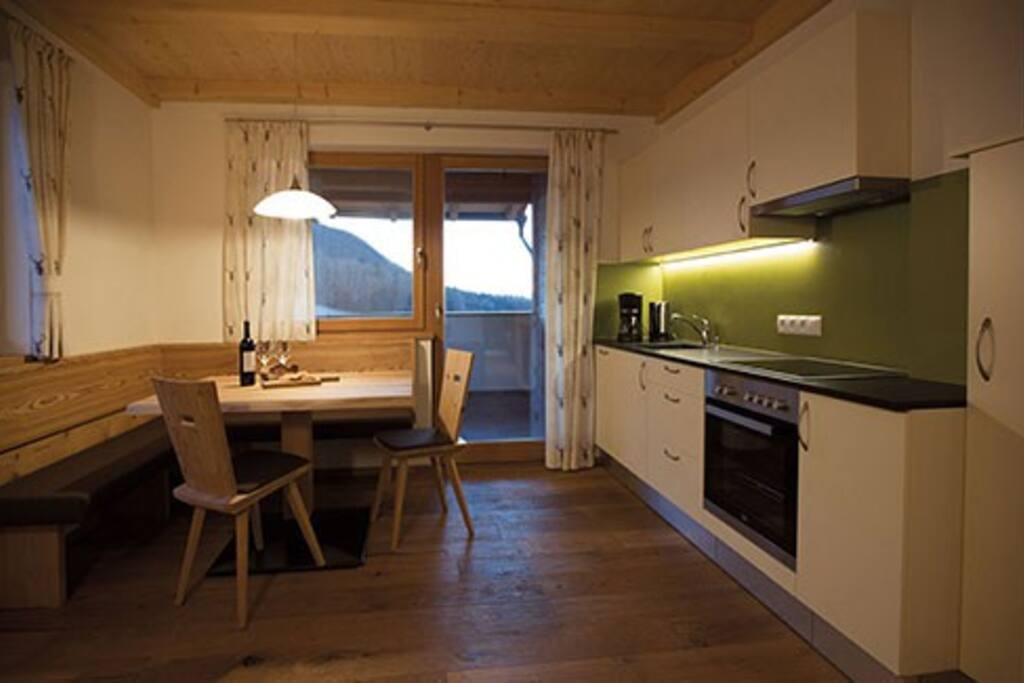 lichtdurchfluteten Wohnküche mit Schlafcouch sowie mit einem Balkon und einer Terrasse