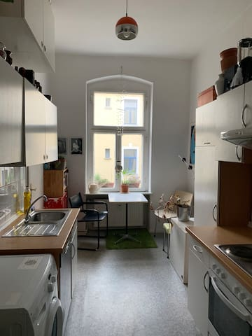 Kitchen with oven, dish washer and wasching maschine and a small table with chairs