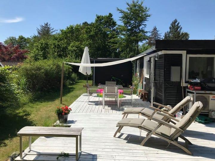Fint lille sommerhus med hems og solrig terrasse
