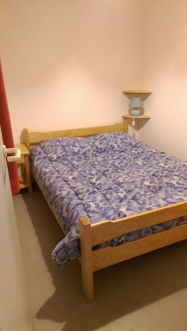 Chambre avec lit de 140 et armoire de rangement et patères, fermée par une porte. Possibilite de mettre un lit parapluie de 60 x 120 en décalant le lit vers la droite