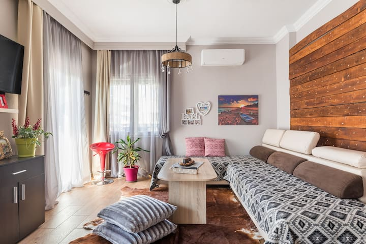 The big living room ,with view to pedestrian street of Kalamaria. Warm and cozy with wooden details. Satellite tv & wifi.