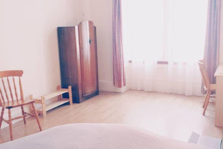 Spacious bedroom, wooden furniture.