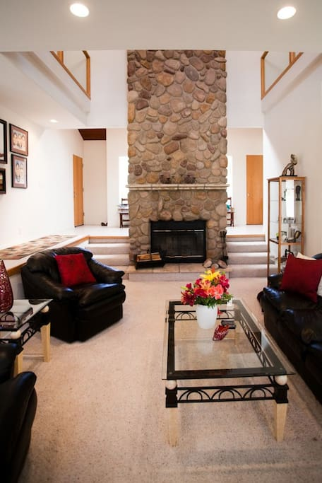 The sunken living room with a wood burning fireplace.