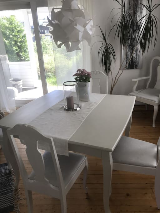 Spisestue med plass til 8  har ekstra lengde på bord og flere stoler. Utgang overbygd terrasse.