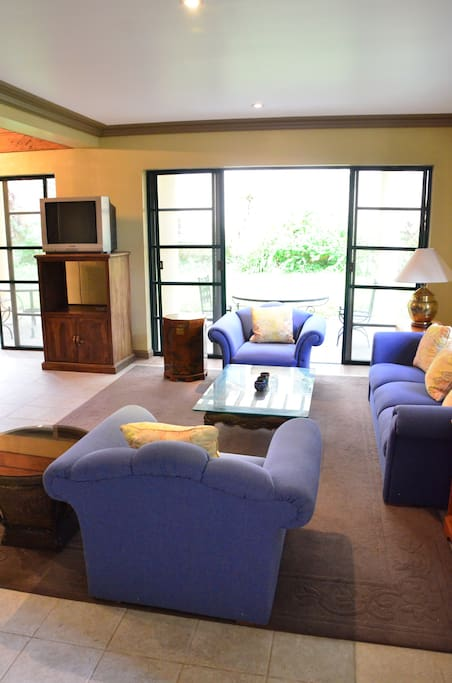 The spacious living room, with wooden flooring and comfortable couches, opens to the grassy lawn.