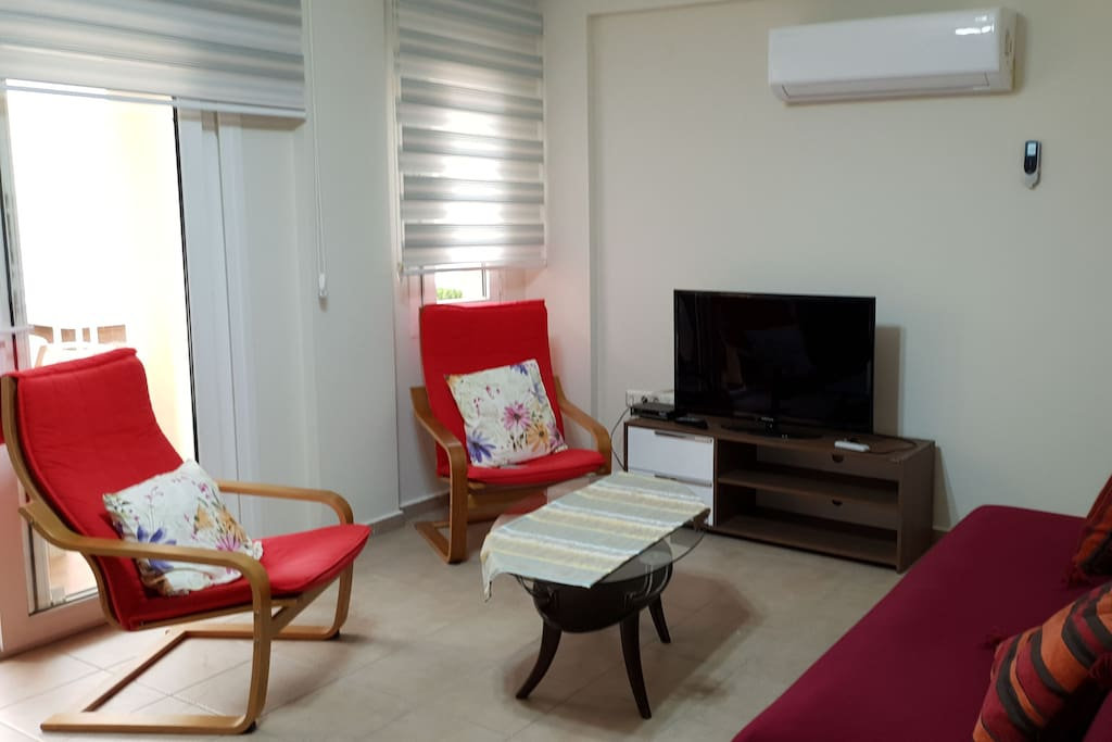lounge with coffee table, blinds and french door leading to balcony