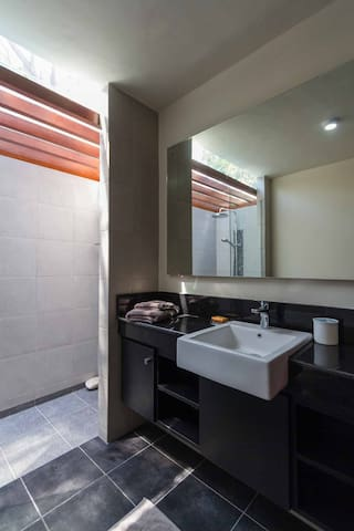 Nicely appointed modern bathroom with open court shower room
