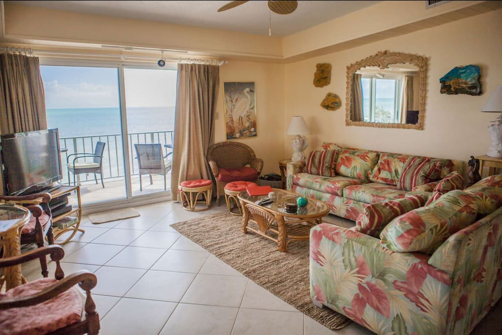 Direct, beachfront views from the spacious living room with seating for 8 & flat screen TV