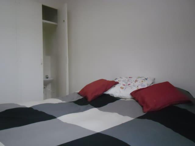 La chambre n°2 avec un lit double ou deux lits simples. Un coin lavabo dans la chambre, un grand placard vide, un velux et une grande fenêtre (double vitrage / volets roulants motorisés).