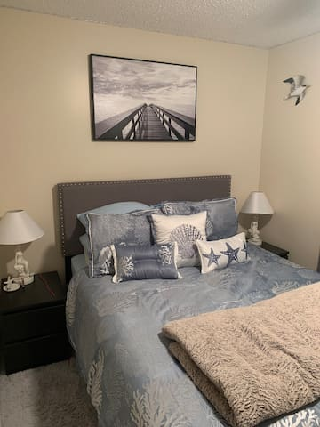 Queen size bed with a nightstand and lamp on both sides. LED strip lights are also wrapped around the entirety of the bedroom ceiling. Ceiling fan.