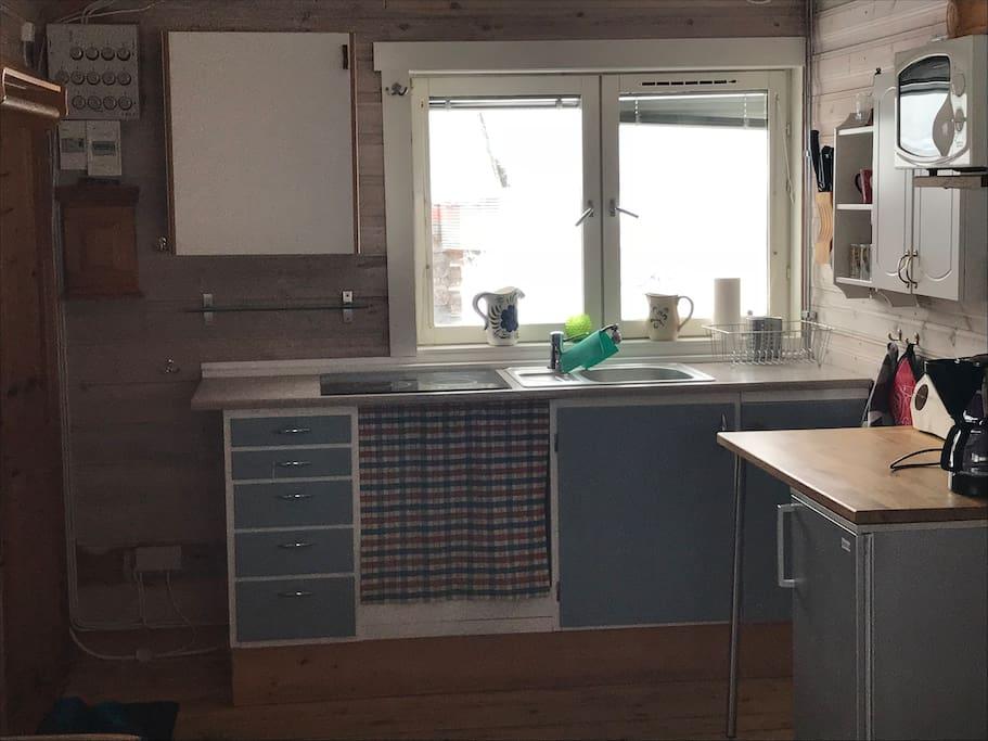 Mindre kök med spishäll, kaffebryggare och microvågsugn.