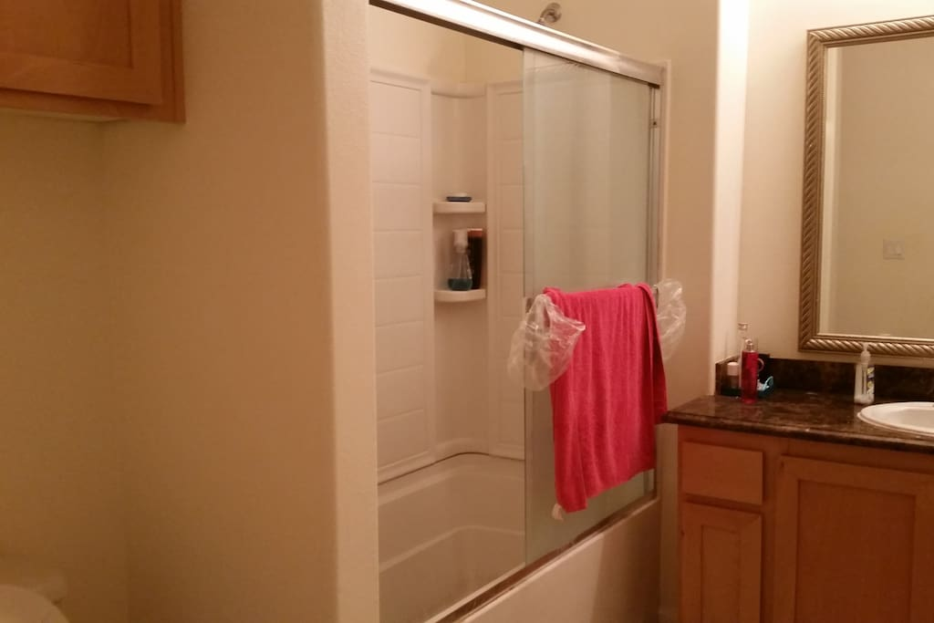 Clean bathroom with bath tub and shower space