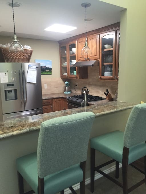 Clean, modern kitchen with skylight, custom cabinets, granite countertops, and gas stove. Stocked with essentials.