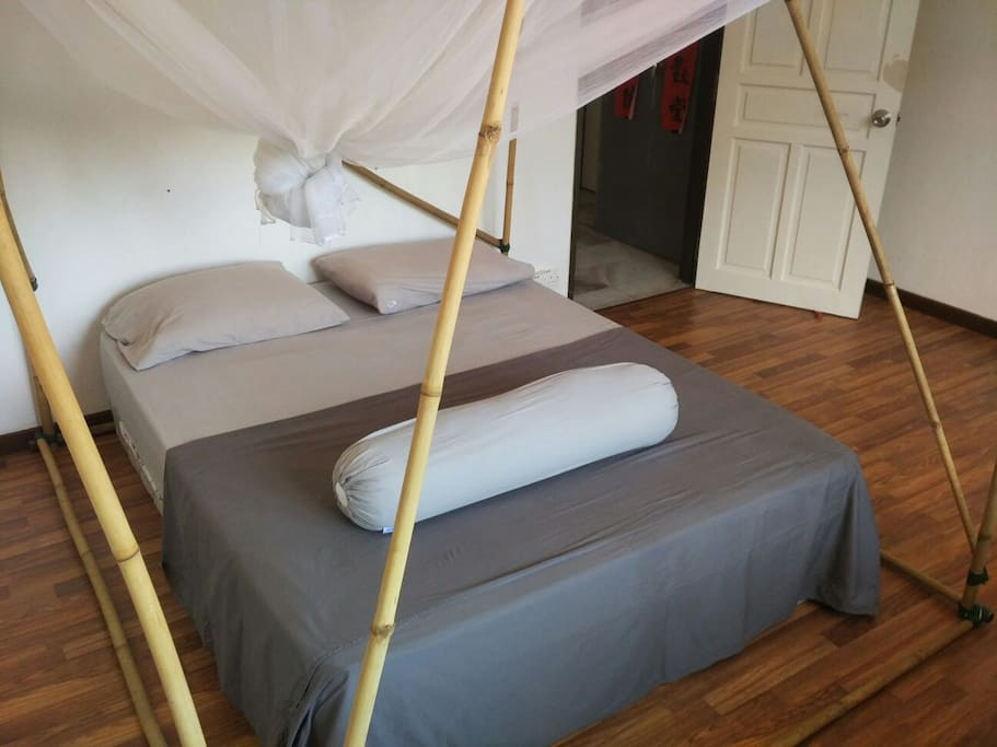 Queen bed, cotton sheets, large white mosquito net, and towels provided.