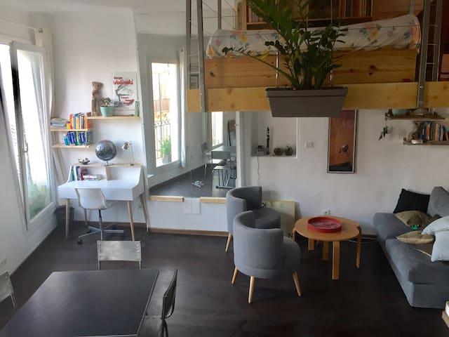 Vue du salon depuis la cuisine, avec le coin bureau, 3 grandes portes fenêtres donnant sur un balcon filant