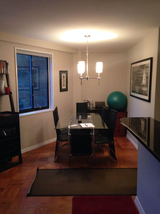Separate living area with dining table and six chairs. Window looking out onto Embassies of New Hampshire Ave.