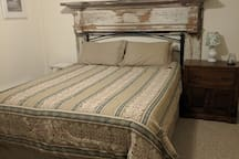 Queen size bed with vintage farmhouse mantel as the headboard.