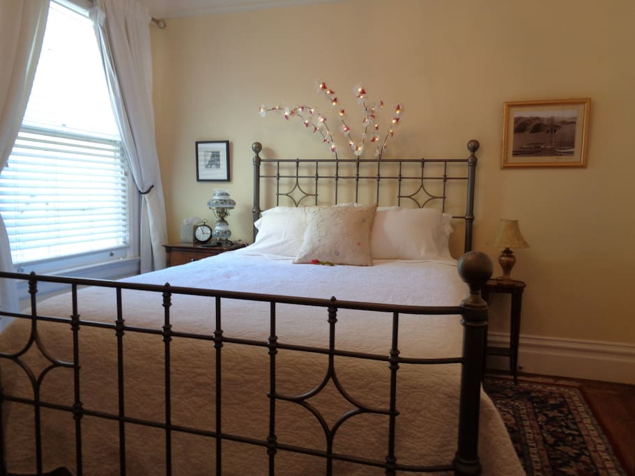 Sumptuous queen bed with soft cotton sheets and a decorative light overhead.