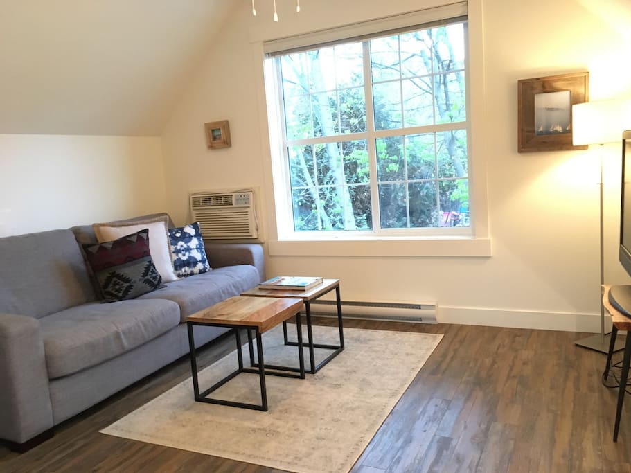 Features a bright and cozy living room with a hightop and two bar chairs, TV with cable, and a view of beautiful green maple leaves in the summer.