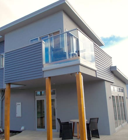 Outside view looking at patio and rear doors that open onto rear deck