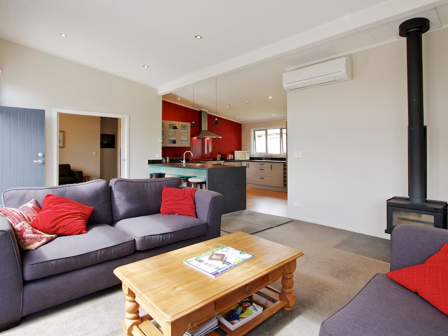 Electric heat pump and wood burning fire place heats house quickly using fan heat transfer ducting system.