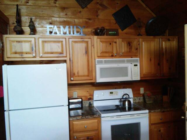 Full kitchen with lots,pans and utensils, glasses and plates. Coffee maker, toaster, blender.