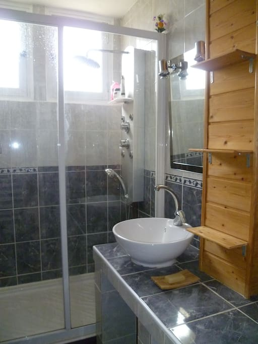 Une grande douche ou la température est réglable très facilement et des étagères pour le rangement